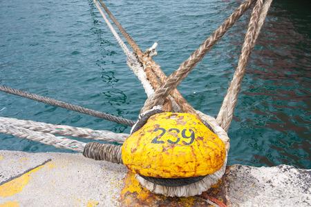 Piraeus, Greece-April 04, 2015: mooring poles braided with mooring ropes Stock Photo