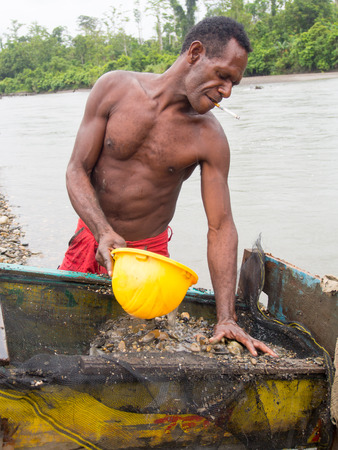 gold rush: The Jungle, Indonesia - January 20, 2015: A man from the Korowaya tribe washing out  gold using a bowl