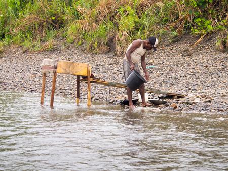 prospector: La Selva, Indonesia - 20 enero 2015: Un hombre de la tribu de lavado Korowaya a cabo utilizando un recipiente de oro Editorial
