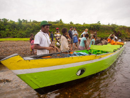 cornrows: Jungle, Indonesia - 20 de enero 2015: Los lugare�os tiran el barco fuera del agua a la orilla del r�o