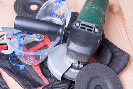 ingenieria elÉctrica: Amoladora eléctrica junto con muelas piezas sobre la mesa de trabajo