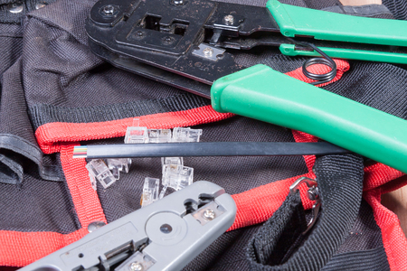 cable cutter: Modular plug crimper. And the modular connector on a work table. Stock Photo