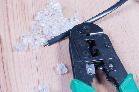 pinchers: Modular plug crimper. And the modular connector on a work table. Stock Photo