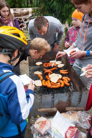 sediento: Otwock, Polonia-23 de mayo 2015: Las personas hambrientas y sedientas acuden al lado de la parrilla de la quema.
