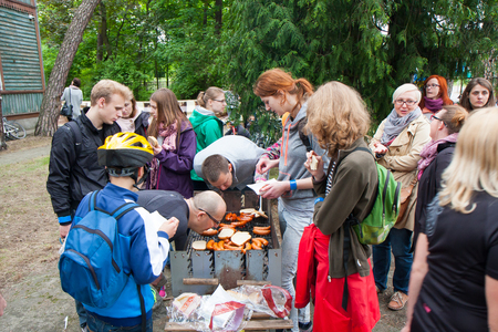 flocking: Otwock, Poland-May 23, 2015: Hungry and thirsty people flocking next to the burning grill. Editorial