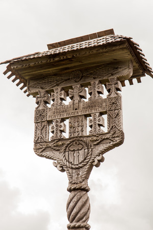sculp: The wooden sculpture in the shape of a cross in front of the Monastery