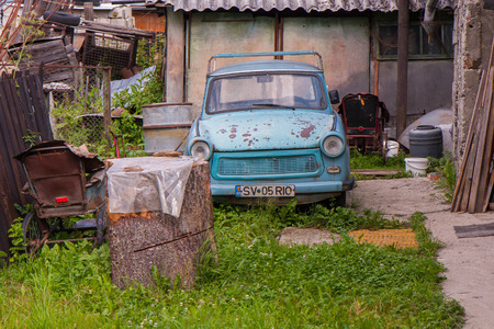 outfield: Suceava, Romania 02 July, 2015: Old wrecked Trabant car among the other untidy stuff