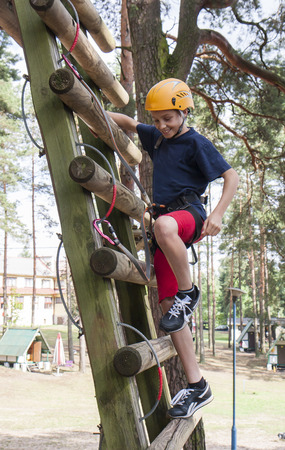 tallness: A boy wearing a safety harness and a helmet walking in a rope park.