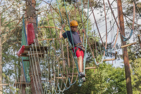 safety harness: A boy wearing a safety harness and a helmet walking in a rope park.