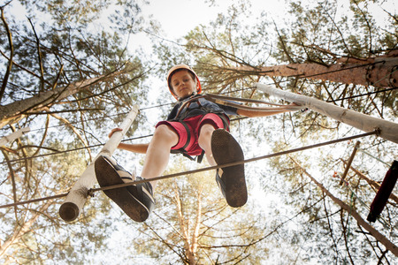 A boy wearing a safety harness and a helmet walking in a rope park.