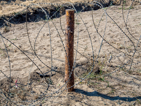abatis: Protections made of barbed wire on a sandy field Stock Photo