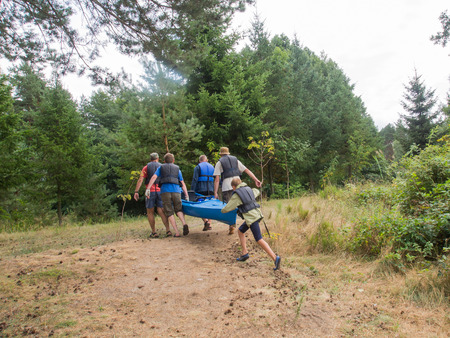 scarp: River Pilawa, Poland - August 25, 2015: Men carrying a loaded kayak over an obstacle Editorial
