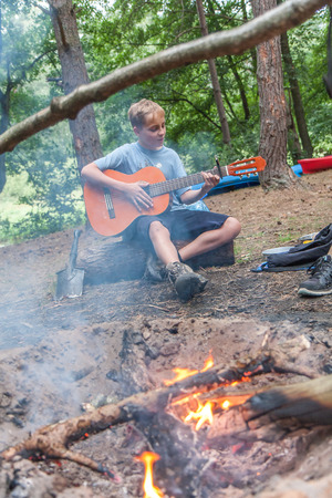 boy playing guitar: A young boy playing  guitar by the campfire at the picnic.