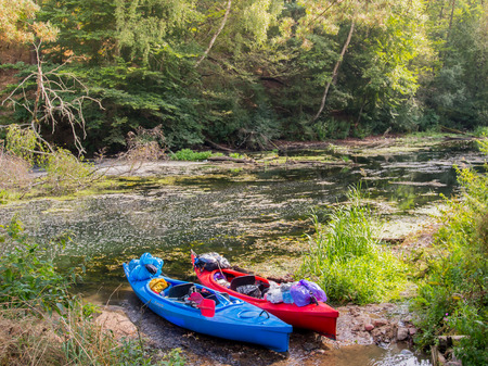 canoeist: River Pilawa, Poland - August 24, 2015: Tourist kayaks are on the river bank covered with trees
