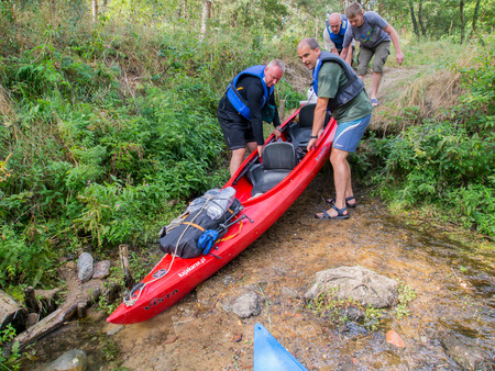 scarp: River Pilawa, Poland - August 24, 2015: A couple of men lift a heavy canoe down a slope to a river