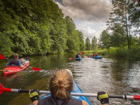 laden: River Pilawa, Poland - August 25, 2015: The Group of kayaks flowing down the river between trees overturned