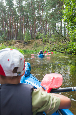 laden: River Pilawa, Poland - August 26, 2015: The Group of kayaks flowing down the river between overturned trees