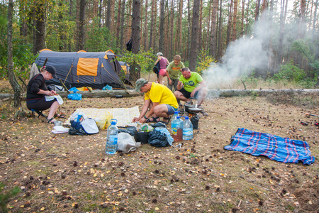 camping pitch: River Plawa, Poland - August 26, 2015: A group of tourists set up a tent in the woods and cook a meal on a campfire