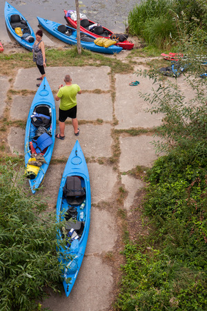 scarp: River Pilawa, Poland - August 27, 2015: Canoes loaded with luggage on a shore. Editorial