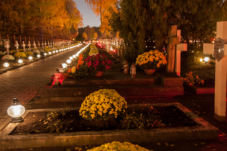 Warsaw, Poland - November 01, 2015: Alley of graves with lighted candles in a Catholic cemetery