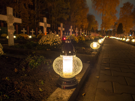votive candle: Warsaw, Poland - November 01, 2015: Alley of graves with lighted candles in a Catholic cemetery