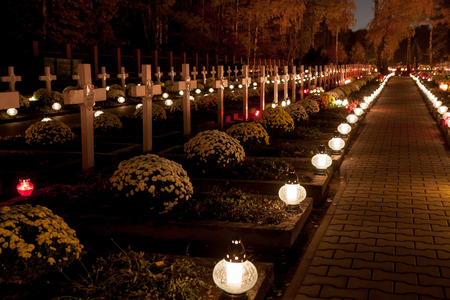 hallowmas: Warsaw, Poland - November 01, 2015: Alley of graves with lighted candles in a Catholic cemetery