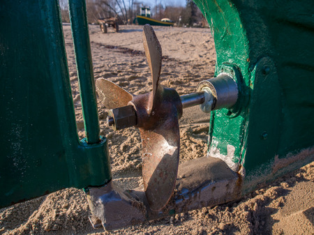 gaff: Steel propeller and rudder of a fishing boat on a sandy beach