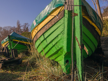 onto: Old destroyed fishing boats pulled onto the grass
