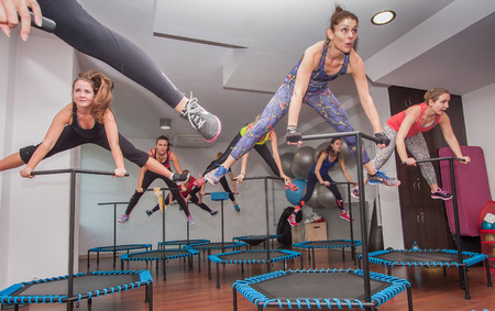 strenuous: Otwock, Poland - November 22, 2015:  Fitness women jumping on small trampolines