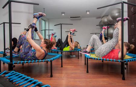 deftness: Otwock, Poland - November 22, 2015:  Fitness women jumping on small trampolines