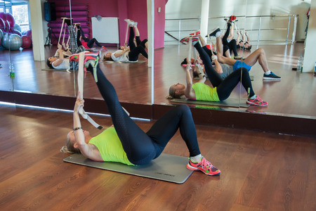 deftness: Otwock, Poland - November 22, 2015:  Young people exercising  fitness workout on the mats