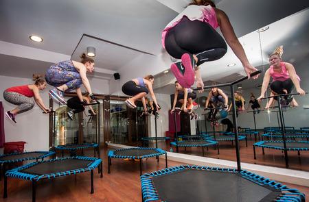 jump: Otwock, Poland - November 22, 2015:  Fitness women jumping on small trampolines
