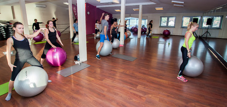 deftness: Otwock, Poland - November 22, 2015: The young people exercising fitness with huge balls