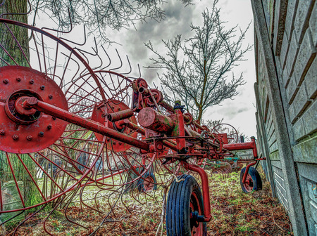 agronomical: An agriculture machine being used to spread out hay