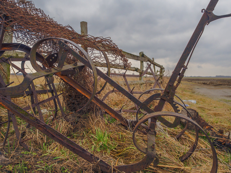 agronomical: An old rusty agriculture machine leaned against the wall
