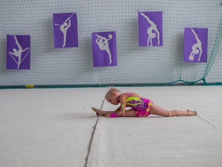 sports field: Warsaw,  Poland -  June 25,  2016:  The competition of art gymnastics. The little girl did the splits during a performance