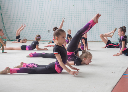 deftness: Warsaw,  Poland -  June 25,  2016:  The competition of art gymnastics. A group of small girls practicing before the competition