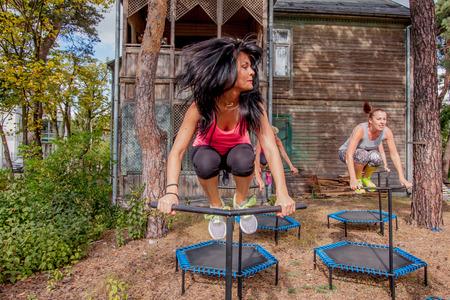 deftness: Otwock, Poland - Septemberr 25, 2016:  Fitness women jumping on small trampolines