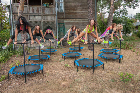 strenuous: Otwock, Poland - Septemberr 25, 2016:  Fitness women jumping on small trampolines