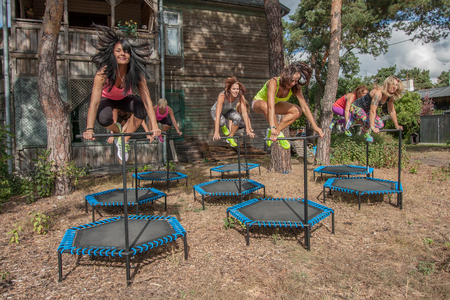 agility people: Otwock, Poland - Septemberr 25, 2016:  Fitness women jumping on small trampolines