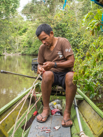 inhabits: Palmari, Brazil - May 06, 2016: Resident of a Amazon jungle fishing  the piranha. Editorial
