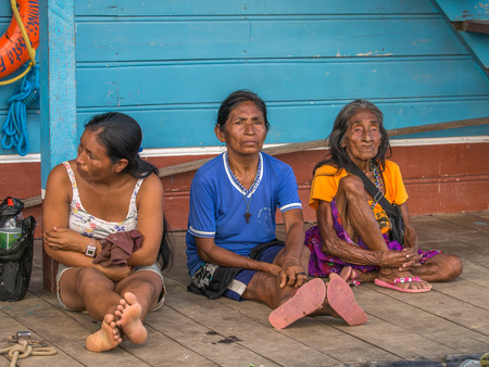 poky: Tabatinga, Brazil - May 05, 2016: Local women of different ages sitting on a pier in the port of Amazon river
