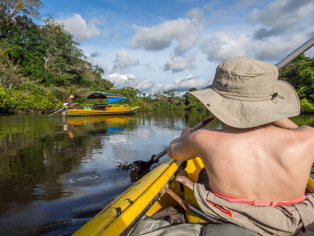 Jangle, Brazil - May 8, 2016: Young women  kayaking between the treetops in the flooded jungle