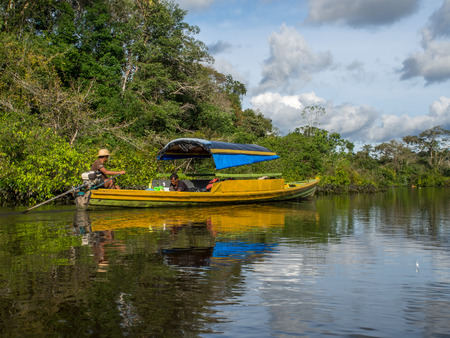 Jangle, Brazil - May 8, 2016: Locals  leading  the small boat on the Amazon river Editorial