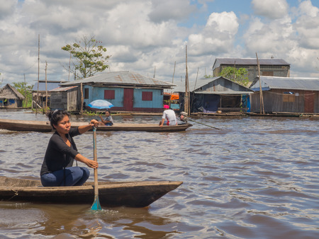 """shantytown: Iquitos, Peru- May 16, 2016: Boat on  water """"road"""" in southern estate. Stock Photo"""