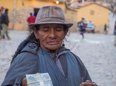 masticate: Ollantaytambo, Peru - May 20, 2016: Woman selling coca on  the  market