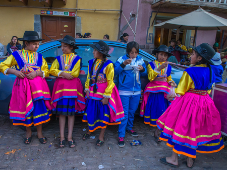 pisac: Pisac, Peru - May 19, 2016: Kids in colorful, folk costumes in the Pisac market