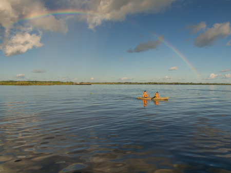 Iquitos, Peru- May 16, 2016: Rainbow over Amazon river and  kayak with the canoeists.
