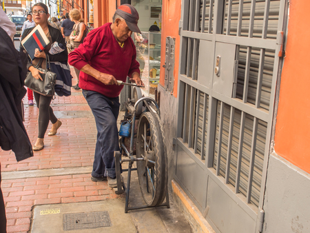 Lima, Peru - May 27, 2016: Man is sharpening the knife on the street of Lima Redakční