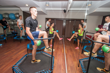 deftness: Otwock, Poland - September 10, 2016:  Fitness. Young people exercise with ball on small trampolines